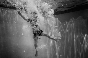 Boy floating in bubbles underwater with legs out