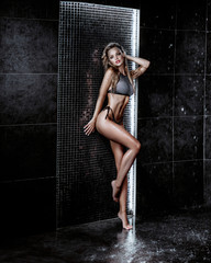 Foto op Canvas Akt Beautiful sexy blonde girl with wet hair. Posing in a swimsuit in the shower under the drops of water