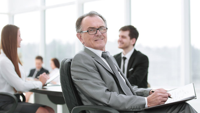 pensive mature businessman in suit with his team working behind