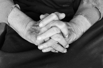Hands of an old woman on her lap - black and white, selective focus
