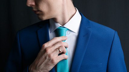 Close-up young man in an suit. He is in a white shirt with a tie. The man straightens his tie, his face unshaven. Businessman in blue costume and turquoise necktie. Dark background