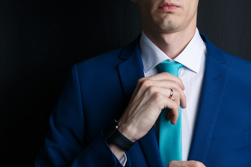 Close-up young man in an suit. He is in a white shirt with a tie. The man straightens his tie, his face unshaven. Businessman in blue costume and turquoise necktie. Dark background. Wrist watches