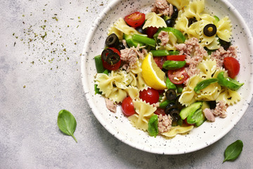 Pasta salad with tuna and vegetables ( cherry tomato, cucumber, green bean and black olives ) . Top view.