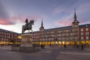 View of Philip lll statue and architecture in Calle Mayor at dusk, Madrid, Spain