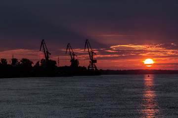 Port cranes and a bloody sunset over the river