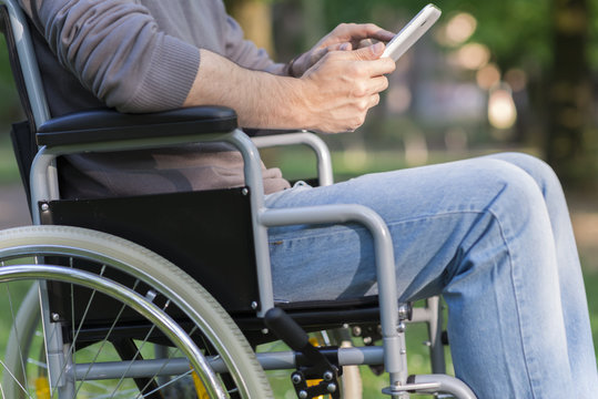 Detail of disabled man using a tablet in a park
