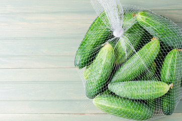 A lot of green cucumbers in net bag. Light wooden background. Space for text. Flat top view