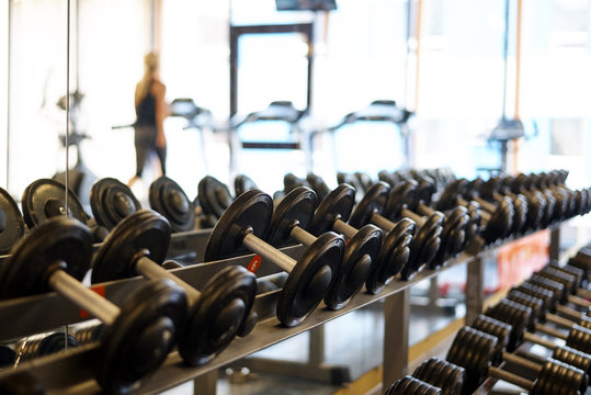 Dumbbells on the rack in the sports hall of the club.