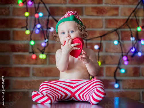 969c3ac027d2d Beautiful little baby boy in elf hat with gift box and fairy lights on  background. Christmas time season image