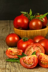 Fresh tomatoes on an old wooden table. Growing of fruits and vegetables. Healthy food. Raw vegetarian food. Sale of tomatoes.