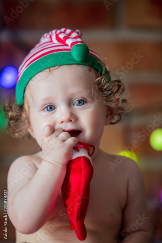 b661eb66c5f32 Little baby boy in elf hat with fairy lights on background. Christmas time  season image
