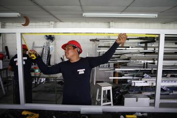 An employee works in an aluminium window frame at Torno Lara Industries in San Salvador