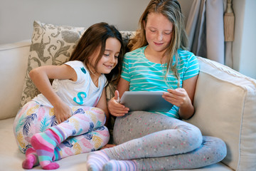 Happy sisters sharing tablet device playing games at home