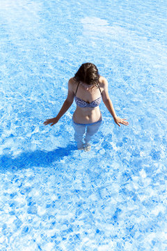 Woman relaxing in a pool in a summer day