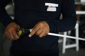An employee works with an aluminium window frame at Torno Lara Industries in San Salvador