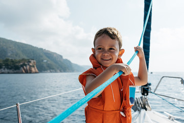 Happy boy holding rope on boat.