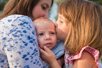 Girl kissing her infant brother in his mother's arms
