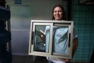 Lariza Lara shows an aluminium window frame at Torno Lara Industries in San Salvador