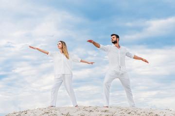 young couple practicing yoga in warrior (Virabhadrasana II) pose on sandy dune