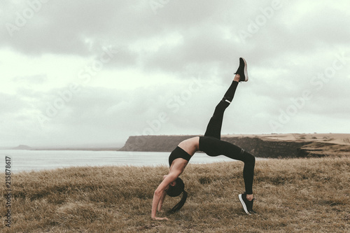 d3eebb8e54b2d Woman practicing one legged wheel pose on field by sea against cloudy sky
