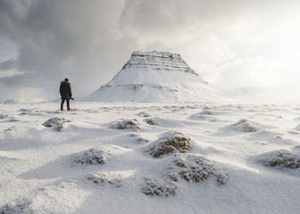 Rear view of man standing on snow covered field against cloudy sky