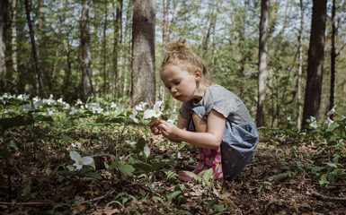 Side view of cute girl looking at white flower while crouching in forest