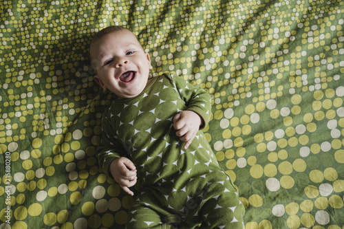a4c650b61 High angle portrait of cute cheerful baby boy lying on bed at home ...