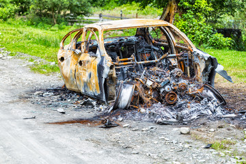 Completely burned car on the country road