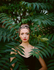 Portrait of beautiful woman among green leaves