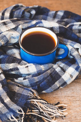 Blue cup of coffee with a knitted scarf on a wooden background