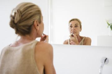 Woman putting lipstick make-up