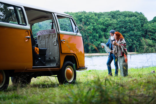 An old hipster couple looks at a road map by their camper van