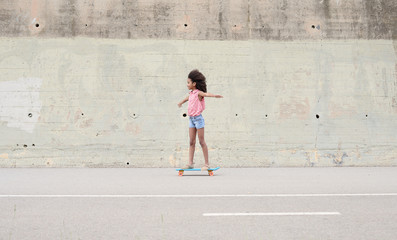 Girl riding skateboard on road