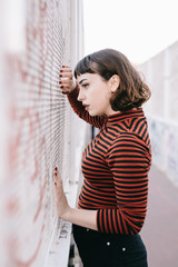 Sad woman leaning on graffiti wall