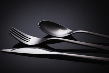 Set of stainless steel cutlery on a black reflective background, Restaurant concept