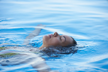 Beautiful Woman tourist in infinity pool of hotel resort enjoying the view over the ocean