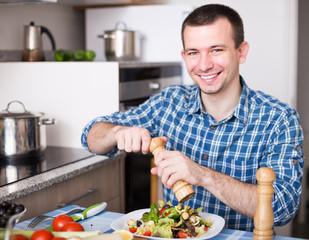 man adding spice to the salad