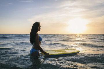 Cute teen girl with a bodyboard at the beach