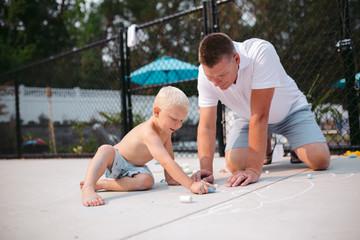 Dad playing with son using sidewalk chalk
