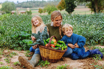 Mom and her kids holding a basket of vegetables in their orchard.