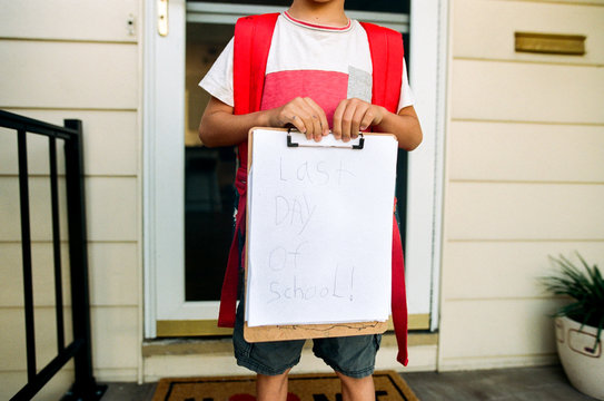 boy holding signage for last day of school