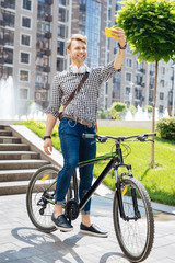 Positive memories. Pleasant happy man smiling while taking photos of himself on the bicycle