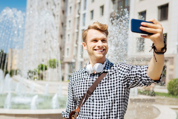 Beautiful view. Happy delighted man standing near the fountain while smiling into the smartphone camera