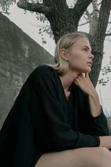 portrait of beautiful blonde girl in black sitting on the street