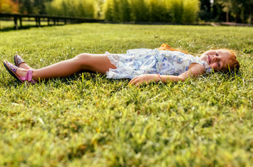 Portrait of a little redheaded girl lying on the grass