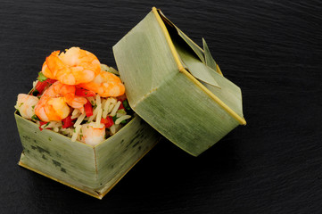 Steamed prawns and rice in bamboo leaf boxes on a slate stone background