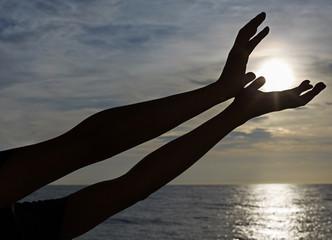 Human hand silhouette, heart shaped, sea sunset background