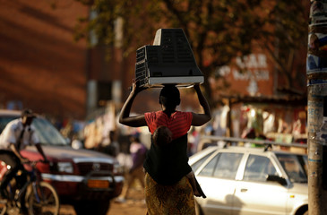 A woman carries a television set on her head and a baby on her back at Mbare township outside the capital Harare