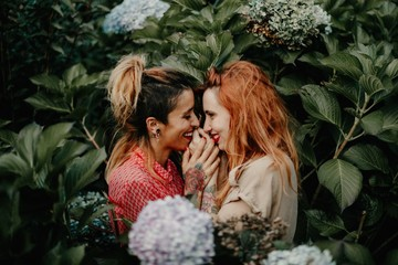 two girls kissing behind a bush