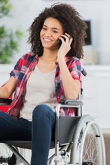 Young woman in wheelchair using cellphone